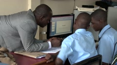 African teacher help school students in computer class-writing article internet Stock Footage