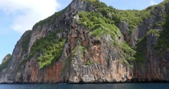 Limestone cliffs with boat off coast of Phuket, Thailand Stock Footage