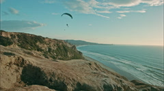 Paragliders flying over ocean Stock Footage