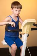 The child is trained on a stationary bike . Healthy lifestyle. Stock Photos