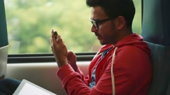 Man using his cellphone and smiling from inside of moving train - stock footage