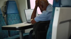Man working on his computer from inside of a moving train Stock Footage