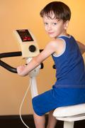 The child is trained on a stationary bike . Healthy lifestyle. - stock photo
