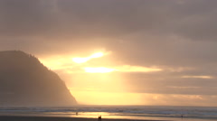 Sunset in Seaside, Oregon on sandy beach with people walking. - stock footage