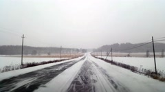 Driving on a country field highway, in terrible snow weather and frozen road - stock footage