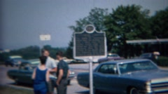 1968: Family outdoor deciding at classic parked cars and historic sign. Stock Footage