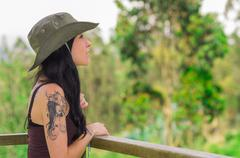 Pretty brunette with tattoos wearing green safari hat standing by railing in - stock photo
