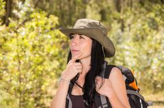 Adventurous brunette trekking in forest environment wearing green safari hat and Stock Photos