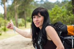 Adventurous brunette, outdoors forest environment wearing backpack, holding Stock Photos
