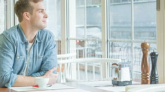 Young man sitting at the table and smiling Stock Footage