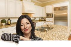 Hispanic Woman Leaning Against White Board In Custom Kitchen Interior. Stock Photos