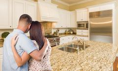 Young Hopeful Military Couple Looking At Beautiful Custom Kitchen. Stock Photos