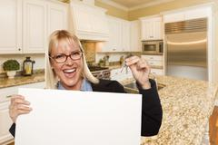 Happy Young Woman Holding Blank Sign and Keys Inside Beautiful Custom Kitchen Stock Photos