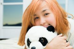 Pretty young woman lying comfortably on white bed and hugging stuffed panda - stock photo