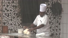 African black chef preparing dough for cooking under heavy rain Stock Footage