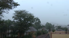 KAMPALA, UGANDA: Tilt down from the rainy sky to a pool in africa - hotel Stock Footage