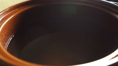 Salting hot water in brown pot Stock Footage
