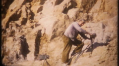 Drill holes, dynamite blasting at rock quarry - 3143 vintage film home movie Stock Footage