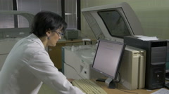 Female technician sets program on computer to lab machine for analyzes blood. - stock footage