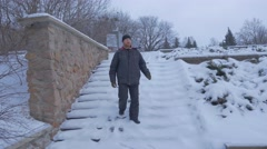 A Bearded Man Going Down a Snowy Winter Staircase, and Moving to Artyom Stock Footage