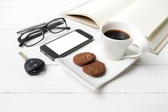 coffee cup with cookie,phone,open notebook,car key and eyeglasses - stock photo