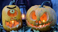 Two terrible pumpkins against dry leaves and an oil lamp Stock Footage