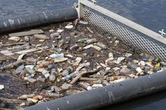 Litter trap with rubbish floating on water Stock Photos