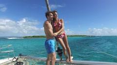 Cheerful couple having fun on a catamaran - stock footage