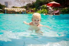 small blonde girl stands looks into distance in water of pool - stock photo