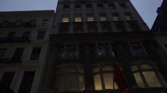 Tall buildings tilting down to Under Armour store at night on Broadway SoHo NYC Stock Footage