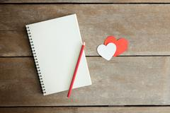 Stock Photo of A pencil on a notebook and a red heart  with morning light in vintage tone