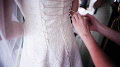 Bridesmaids buttoning on wedding dress - stock footage