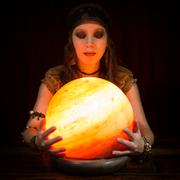 Young pretty fortune teller with a crystal ball, dark background - stock photo