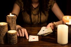 Female psychic is telling the future with cards, concept tarot and card reade - stock photo