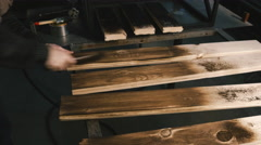 Carpenter cleans burned board. Close-up Stock Footage