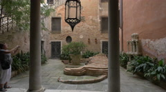 Woman talking pictures of a lion sculpture in an interior courtyard, Venice Stock Footage