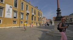 People walking in Campo Santo Stefano, on a sunny day in Venice Stock Footage