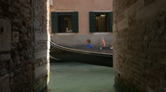 Canal with gondolas seen between two buildings in Venice Stock Footage