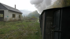View of Mocanita riding next to an abandoned building and trees Stock Footage