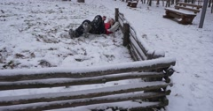 Man is Lying on a Snow And Talking by Phone Stomping by His Legs Man in Red Arkistovideo