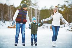 Family in outdoor rink Stock Photos