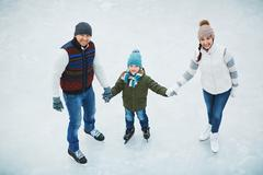 Family in skating rink - stock photo