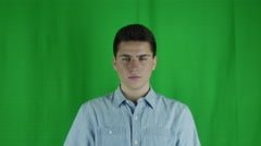 Young man shakes head in front of a greenscreen in a blue shirt Stock Footage