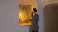 A Religious Middle Aged Man Bows to Saint Mary Icon in Chalk Caves of Stock Footage