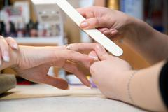 Female hands make manicure by nailfile for woman Stock Photos