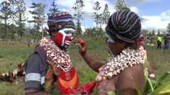 Papuan woman paint the face of a man  - stock footage