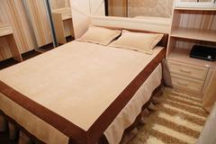 Bed in the bedroom in shades of brown - stock photo