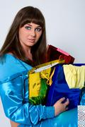 Portrait of blue-eyed brunette with multi-colored packages Stock Photos