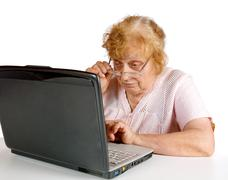 The old woman  looks at the screen notebook - stock photo