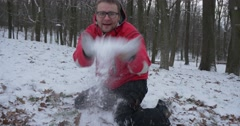 Man is Sitting on His Knees And Throws a Snow Then Lying on His Back to a Stock Footage